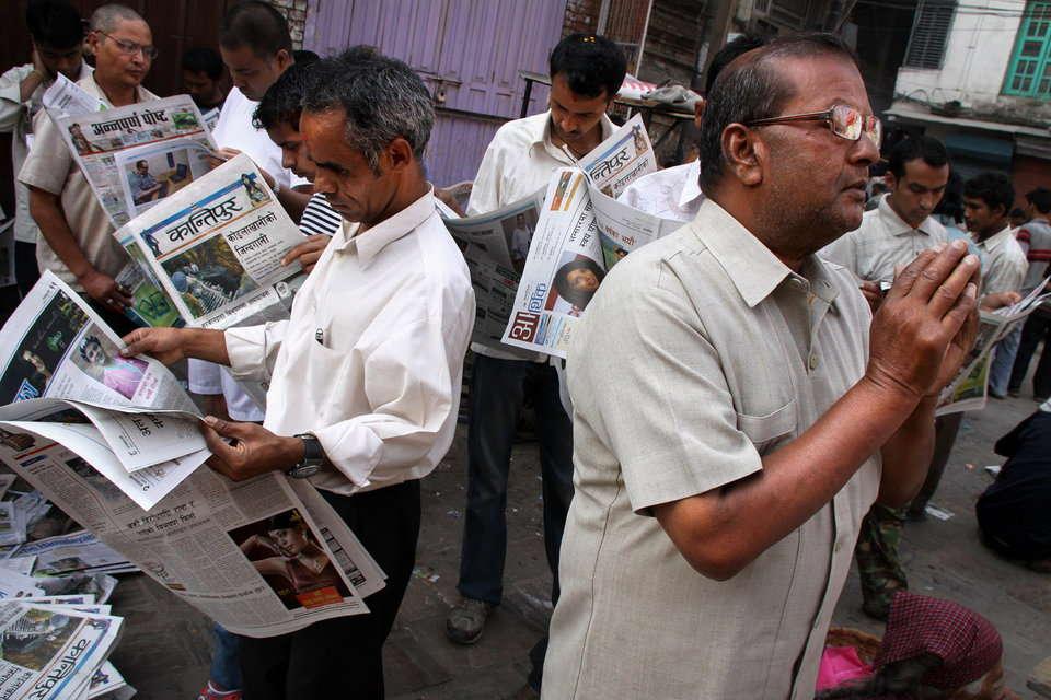 1日の始まりに新聞を読む男達
