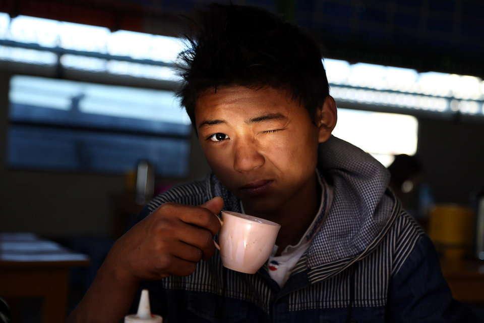 食堂でコーヒーをすする少年