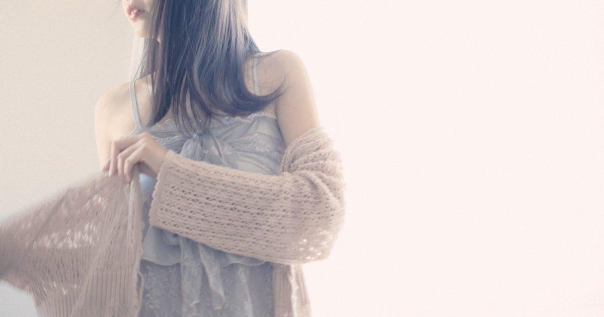 薄手のトッパーカーディガンに袖を通す女性