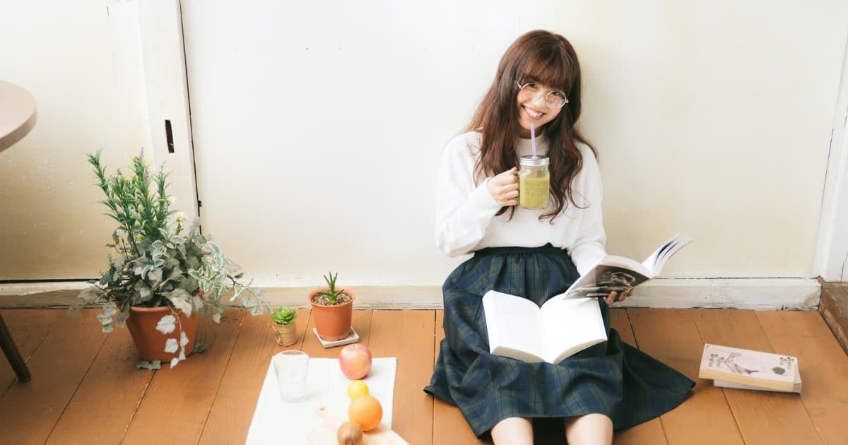 部屋で読書しながらスムージーを飲む美少女