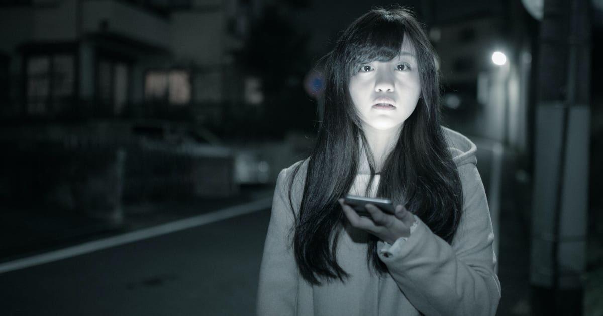 深夜にスマホの明かりで立つ美少女