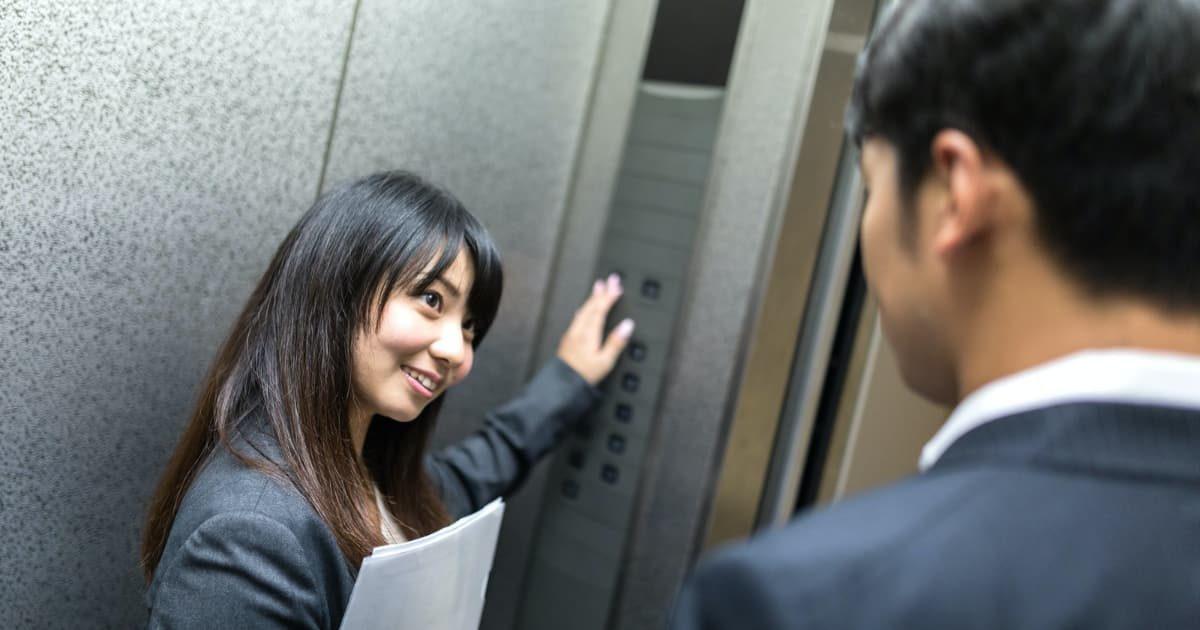 エレベーターのボタンを押す美女