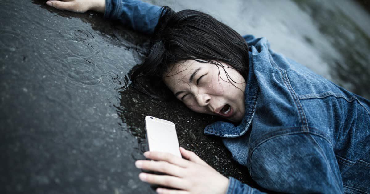 雨の中、スマホを持って変顔で地面に倒れる女性