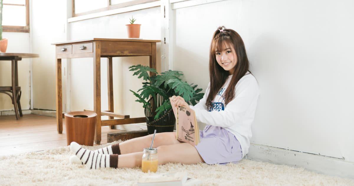 部屋に一人で座り読書しながらスムージーを飲む美少女