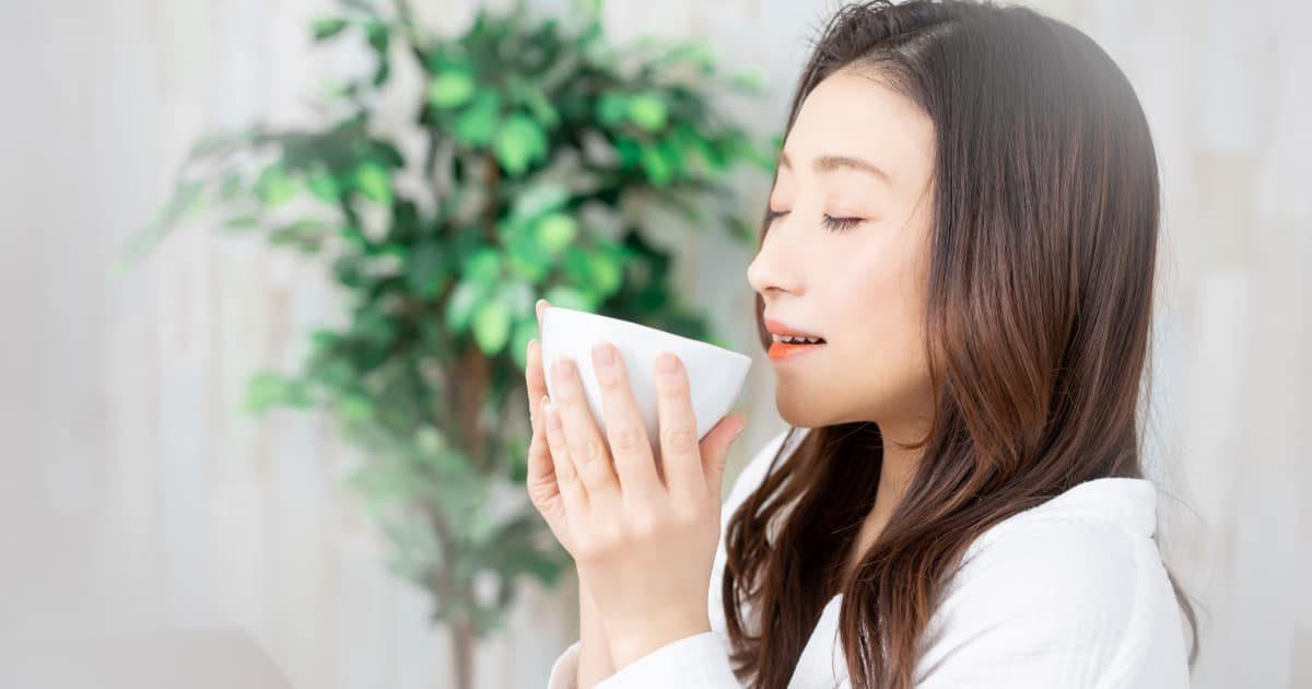 カップの何かを飲む女性