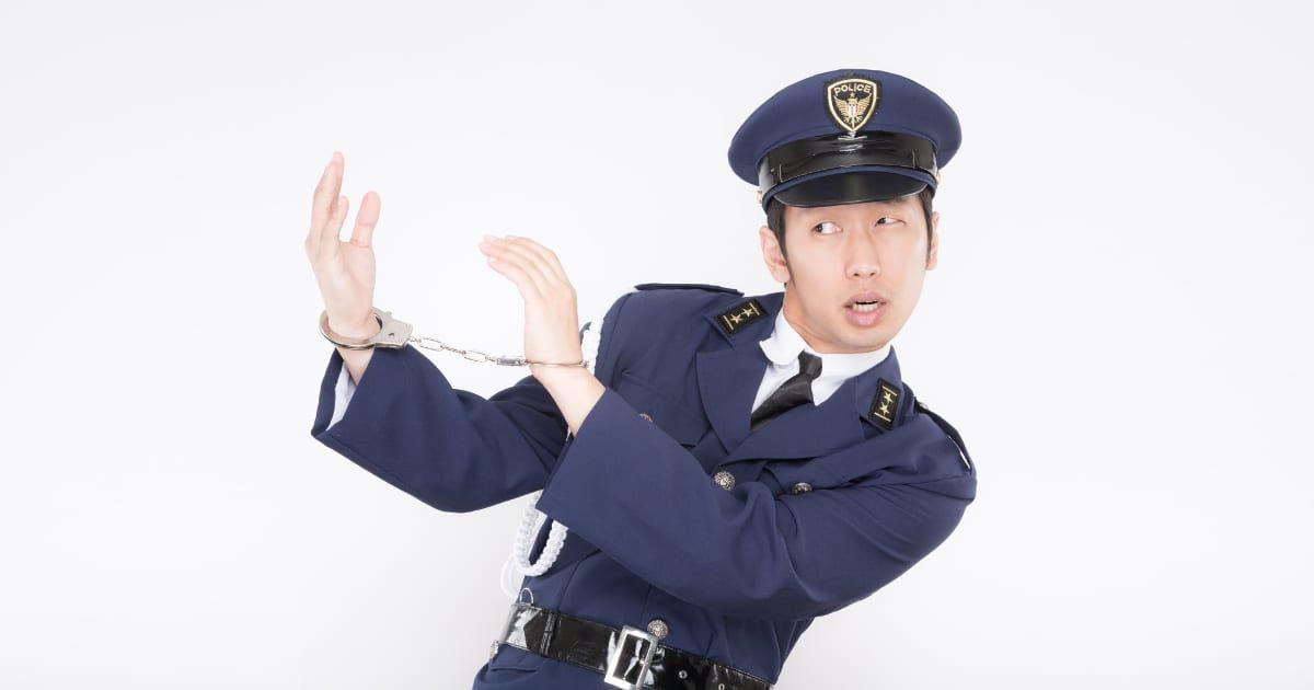 逮捕されて手錠をする警察官