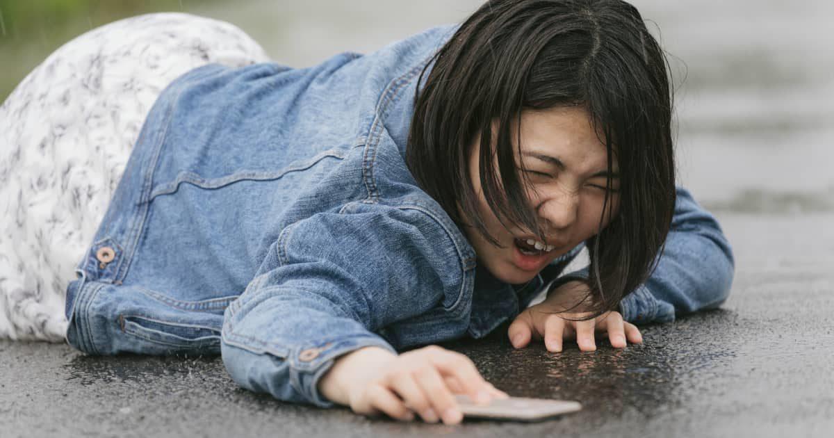 歩きスマホで転倒し泣き叫ぶ女性(雨天)