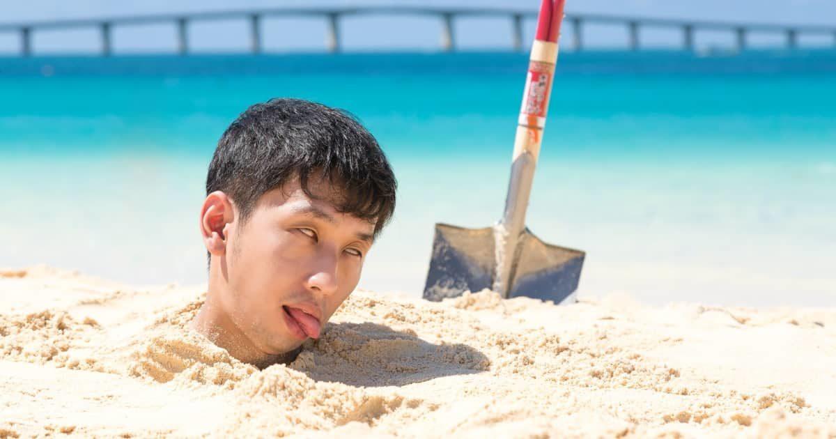 砂浜に首まで埋まる男性
