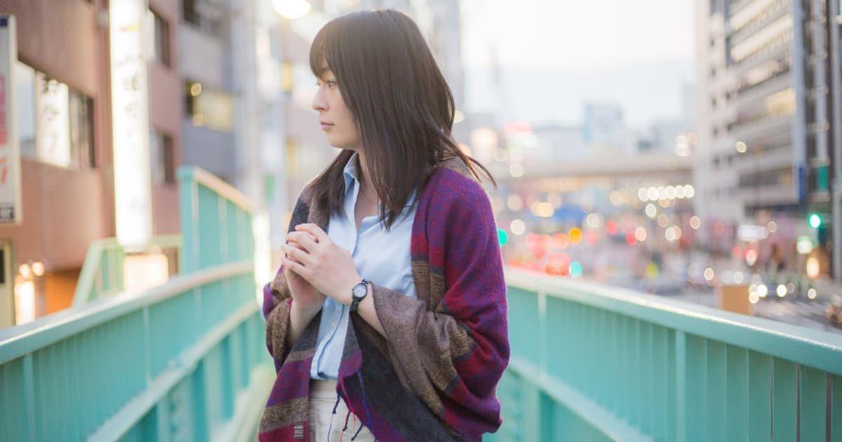 歩道橋の上で立ち止まる女性