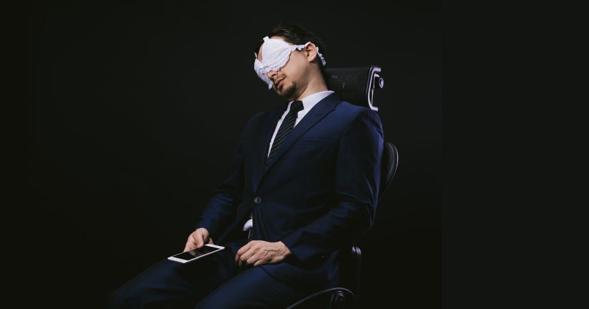 ブラジャーをアイマスクにして寝るスーツの男性