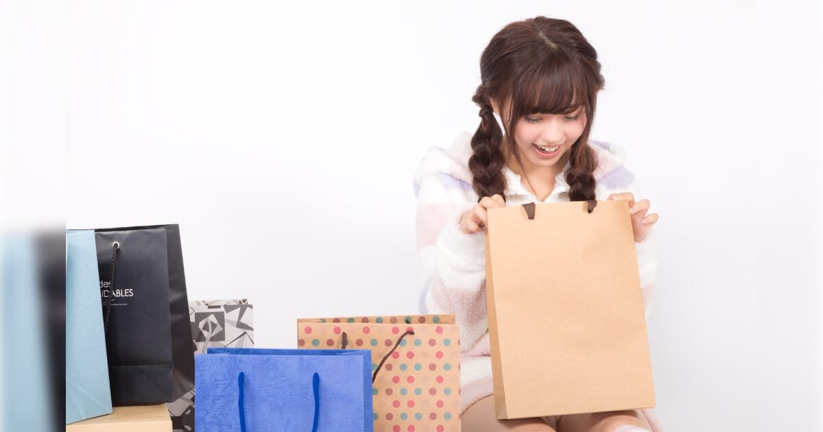 買い物袋の中身を覗く美少女