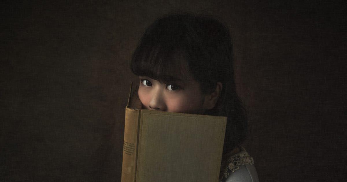本で顔を隠す美少女