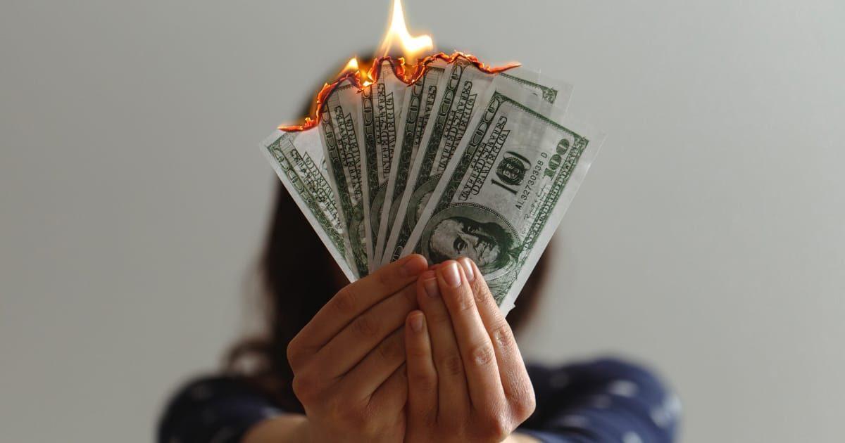 手に持った100ドル札を焼く女性