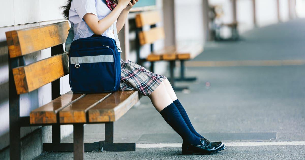 駅のベンチに座る女子高生
