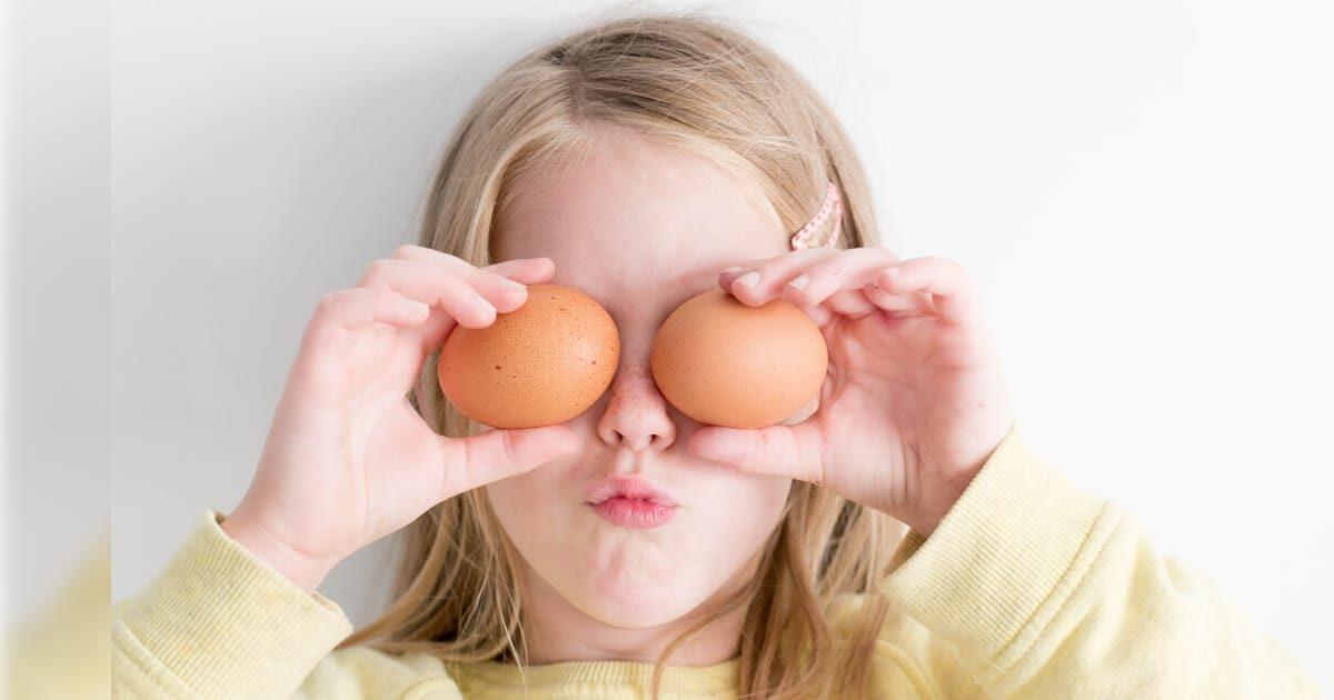 卵を2個持って目を隠す外国人少女