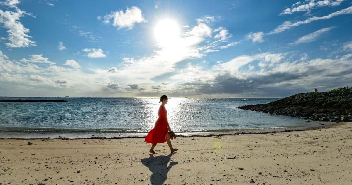 沖縄の海岸を歩く女性